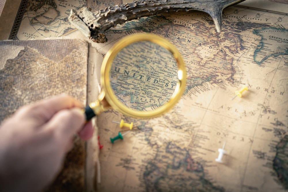 Aktive Fonds vs ETF - Lupe vergrößert Landkarte genaue Suche