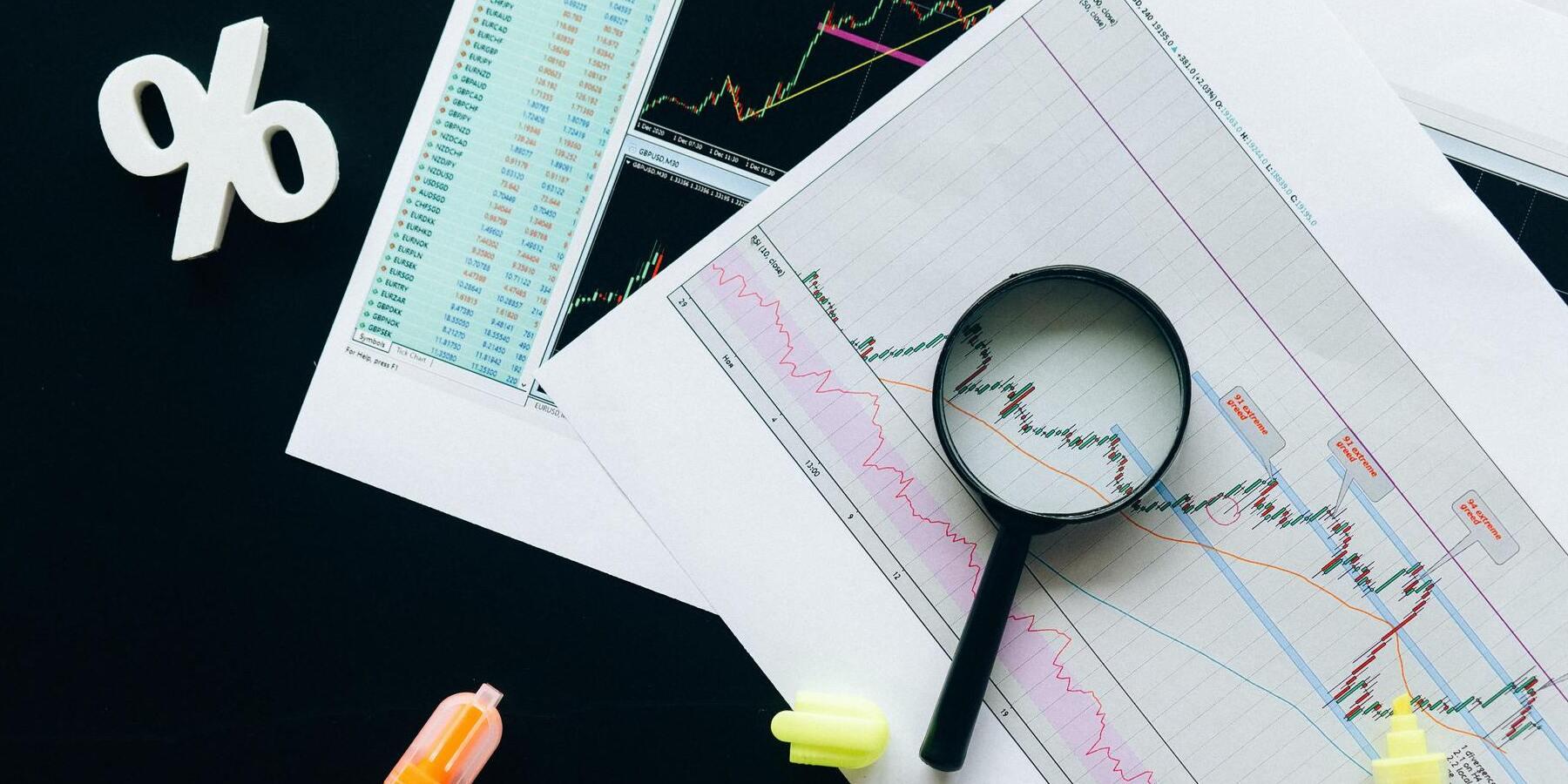 GameStop-Aktie Folgen für den Markt - Charts und Lupe auf Schreibtisch